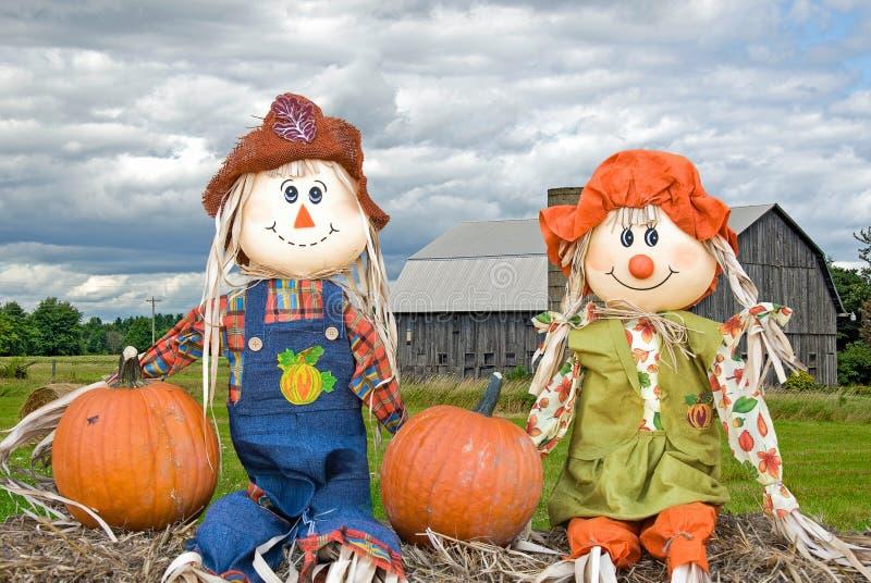 Autumn scarecrows with pumpkins royalty free stock photos