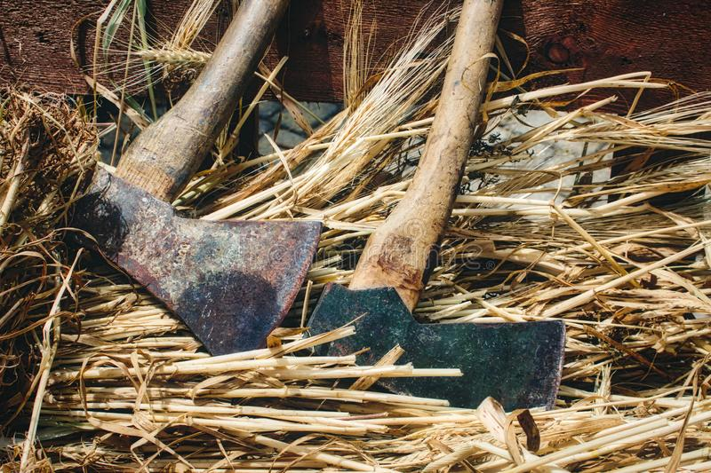 A pair of axes for chopping wood against straw background. A pair of axes for chopping wood against a straw background royalty free stock photos