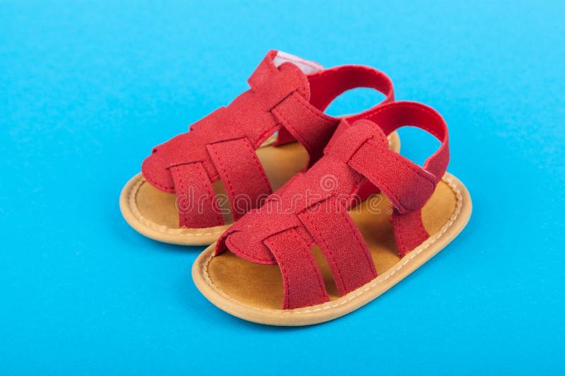 Pair of baby sandals shoes on blue background royalty free stock photo