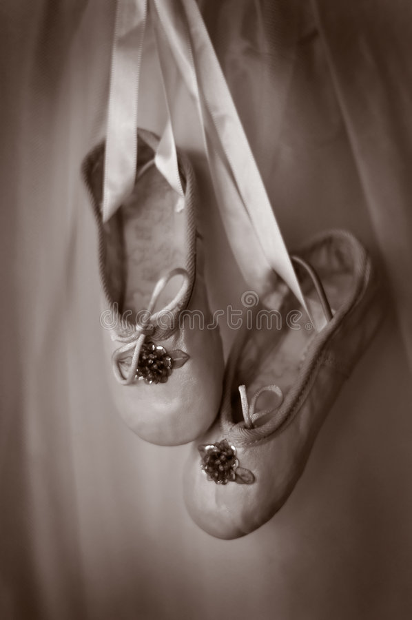 A pair of ballet slippers. A pair of dance or ballet slippers hanging on a wall in a sepia tone royalty free stock photos