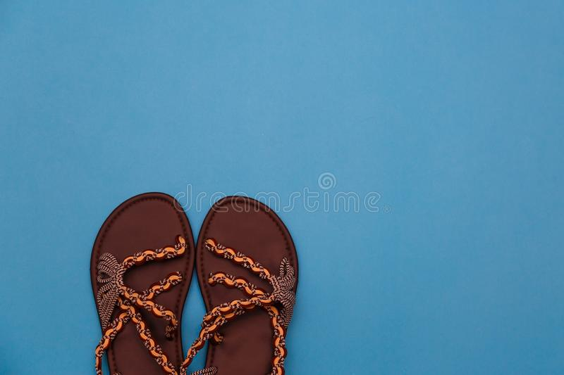 Pair of beach flip-flops on the blue background summer concept. Minimalist flat lay photo of beach flip-flops with some copy space stock photos
