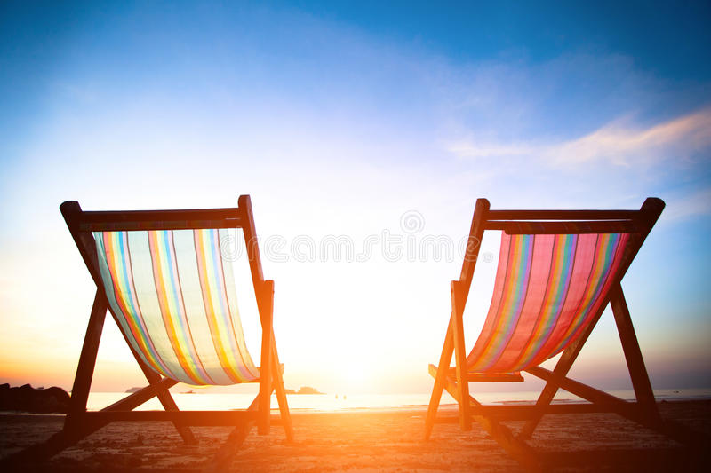 Pair of beach loungers on the deserted coast sea at sunrise royalty free stock photos