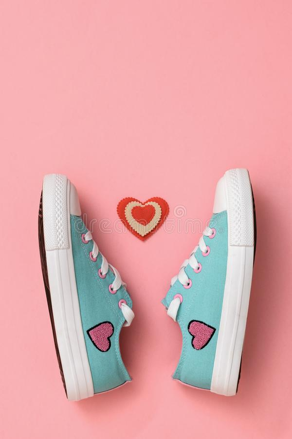 A pair of beautiful sneakers and a red and white heart on a pink background. Color trend 2019. Sports style. Flat lay. The view from the top royalty free stock photos