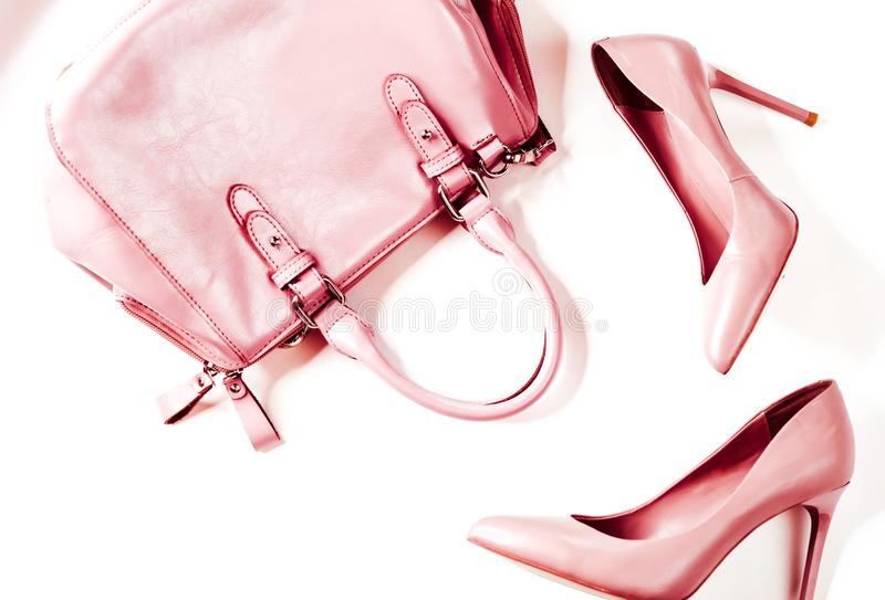 Pair of beige nude women's high-heeled shoes with handbag on a white background top view, flat lay, fashion concept royalty free stock photo