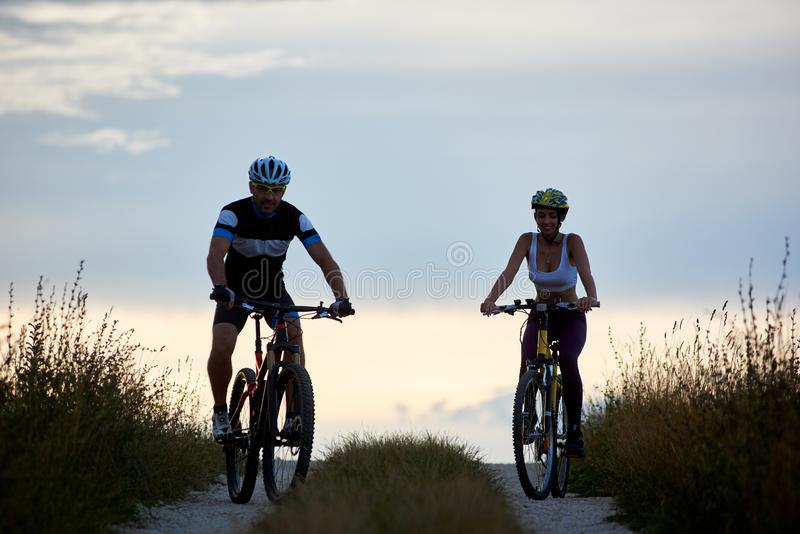 Pair of bicyclist riding bikes on country road. Fit young people in sportswear cycling downhill stock photo