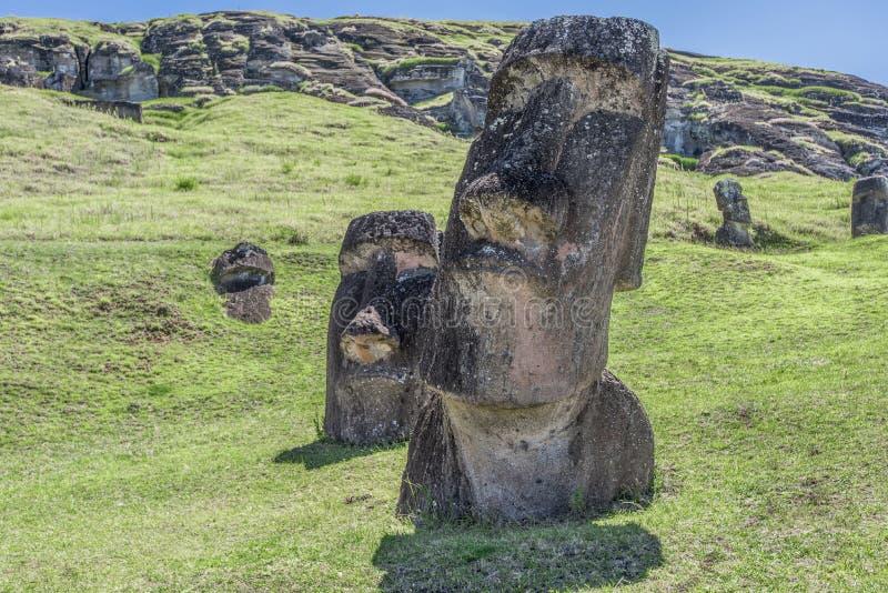 Pair of big underground sculture of moai on the extinct volcano Rano Raraku royalty free stock photo