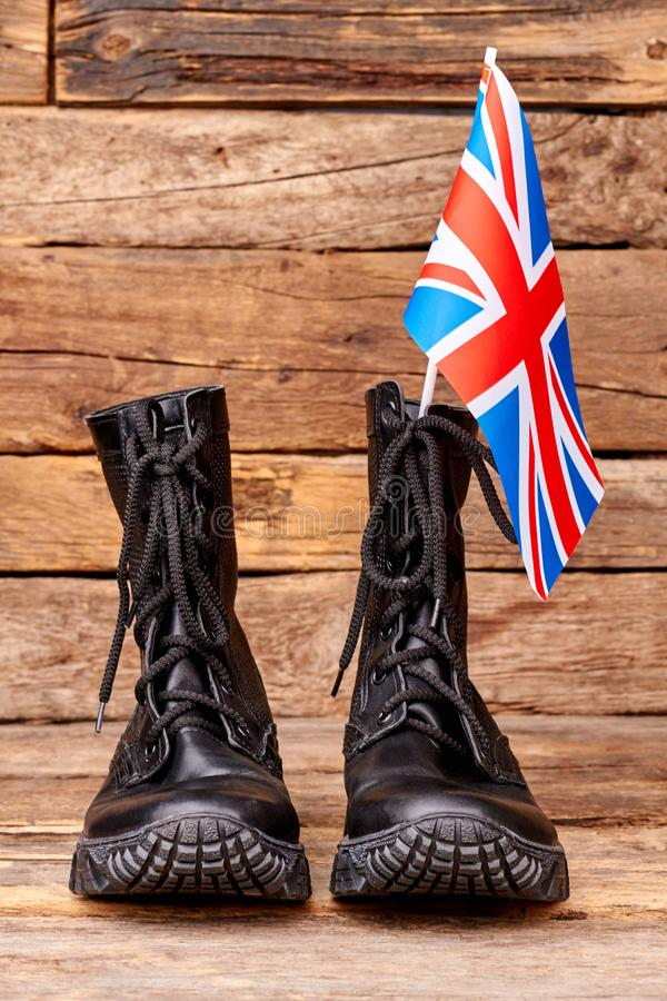 Pair of black combat boots with britain flag. Wooden desk surface background stock image