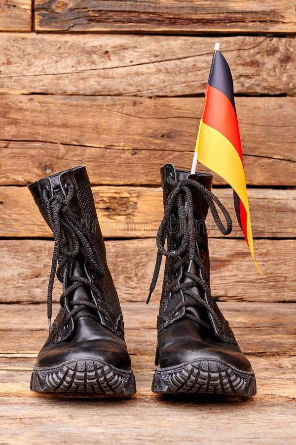 Pair of black combat boots with flag of Germany. Wooden desk surface background royalty free stock photos