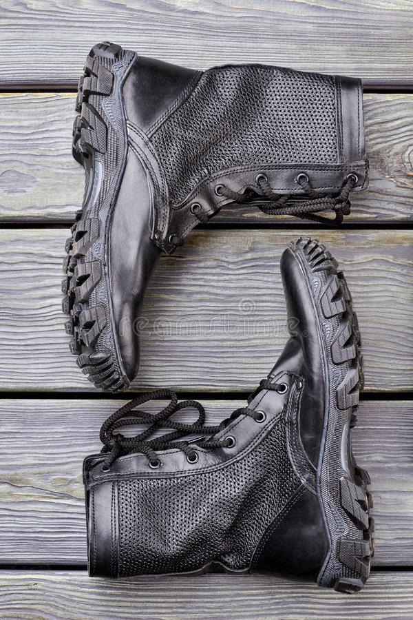 Pair of black combat boots, top view. Flat lay. Wooden desk background royalty free stock photo