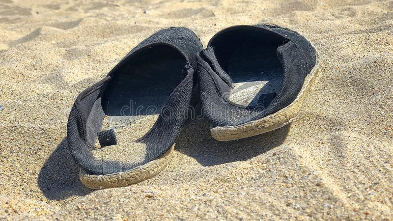 Pair of black espadrilles on the sand. Shot to a pair of black espadrilles lying on the sand royalty free stock images