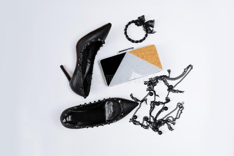 Pair of black shoes decorated with metal accents, jewelery with black lace and beads and a tricolor clutch with sparkles on a stock photos