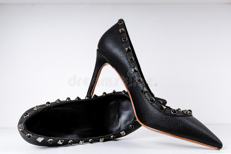 Pair of black high-heeled shoes with pointed toes, decorated with metal inserts against a shelf in the store stock photography