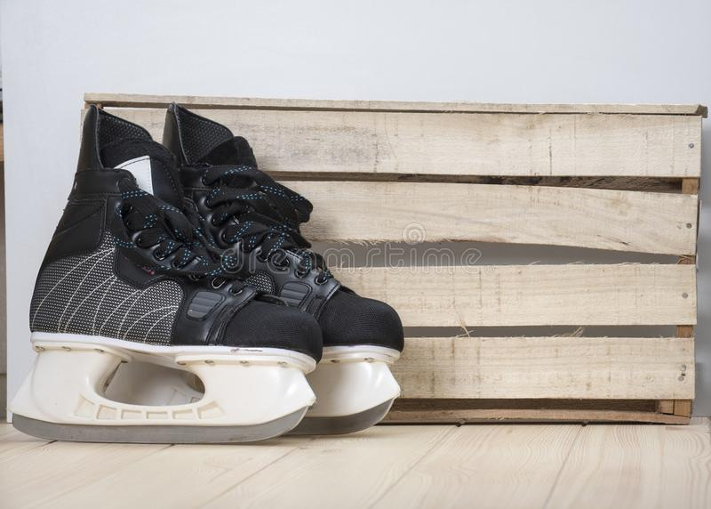 Pair of black hockey skates on a wooden tabletop stock photos