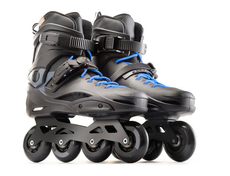 Pair of black inline skates on white. Background royalty free stock image