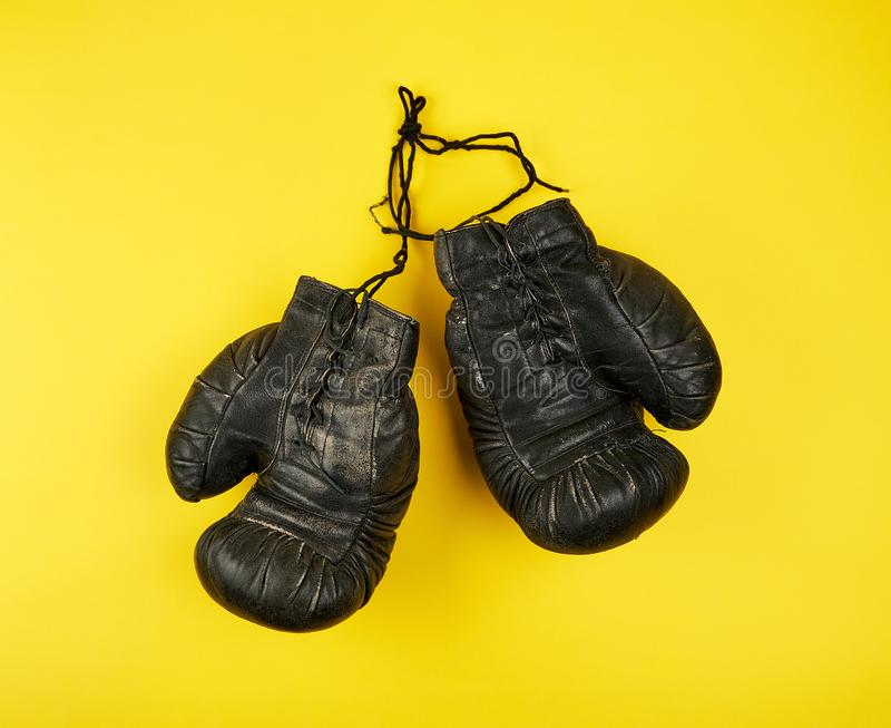Pair of black leather very old boxing gloves on a yellow  background. Top view royalty free stock images