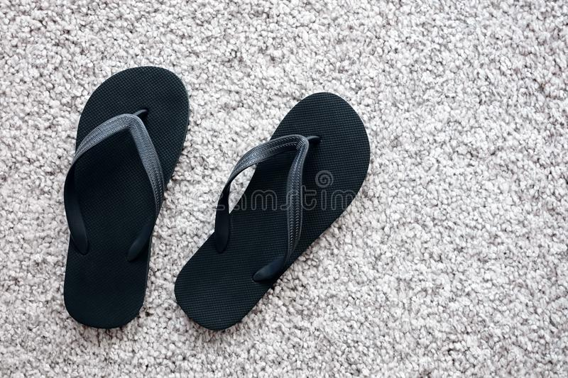 Pair of black rubber flip flops on white carpet royalty free stock images