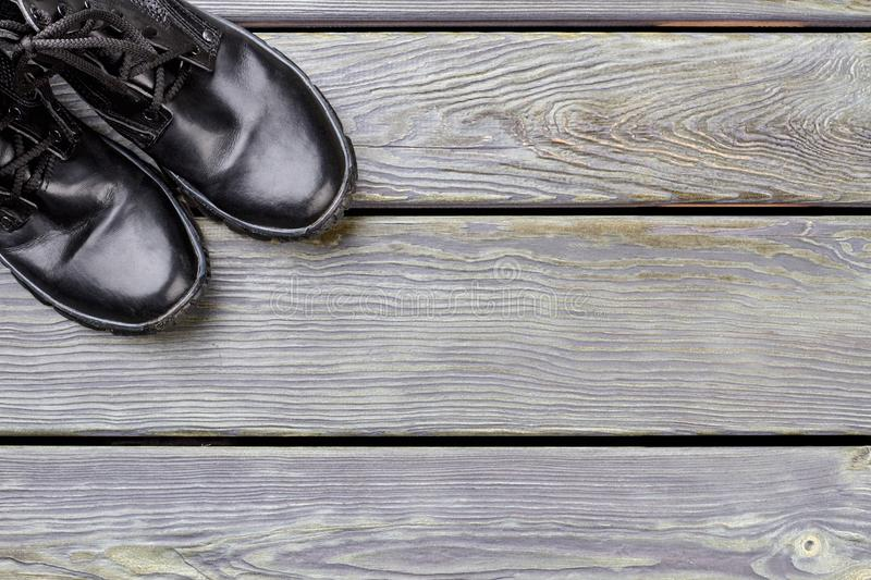 Pair of black shiny combat shoes on wood with copyspace. Top view, flat lay royalty free stock photo