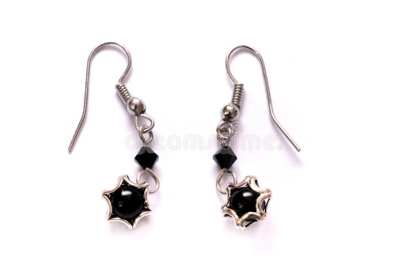 A pair of black star shaped lobe earrings stock images