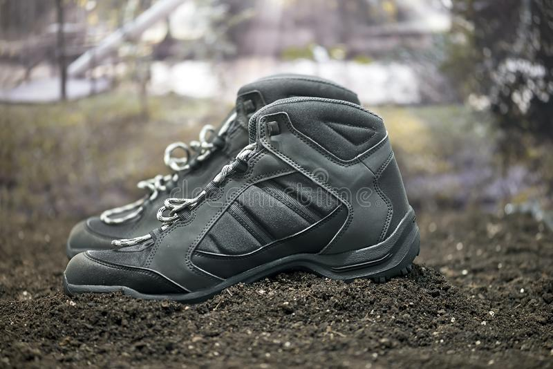 A pair of a black walking boots. On the ground royalty free stock photos