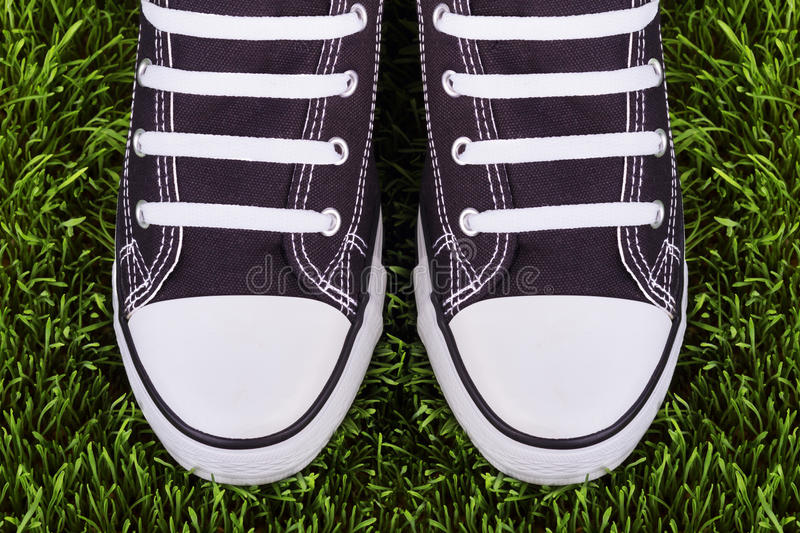 Pair of black and white sneakers on green meadow stock images
