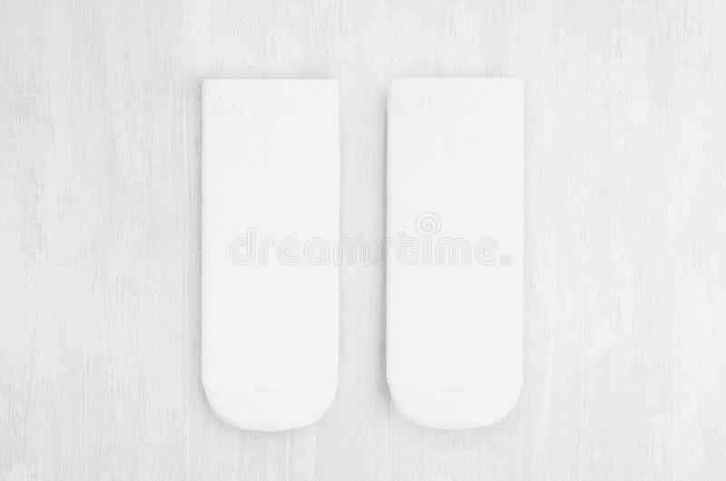 Pair blank white medium socks flat lay on white wood board, front view - mock up for design, print, presentation, advertising. Pair blank white medium socks royalty free stock image