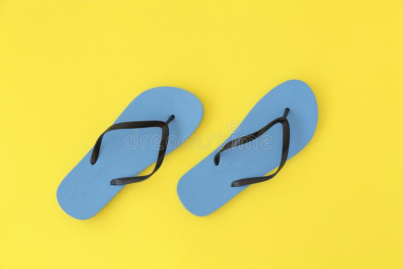 Pair of blue beach flip-flops on the yellow background summer concept. Minimalist flat lay photo of beach flip-flops. With copy space stock image