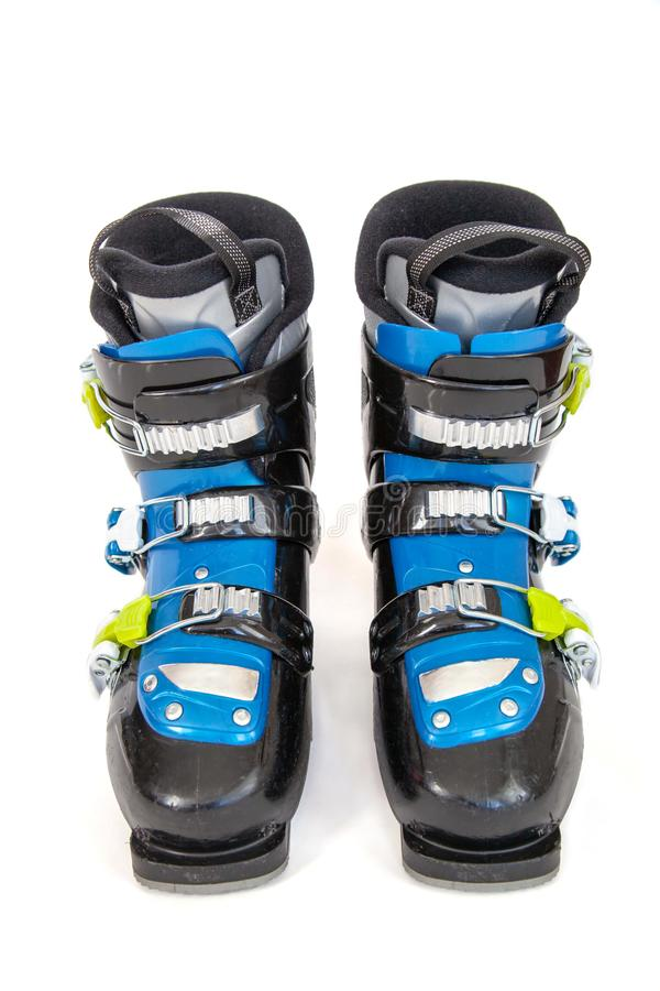 Pair of Blue and Black Ski Boots Isolated on White Background. Pair of blue and black alpine ski boots with yellow buckles isolated on white background royalty free stock photography