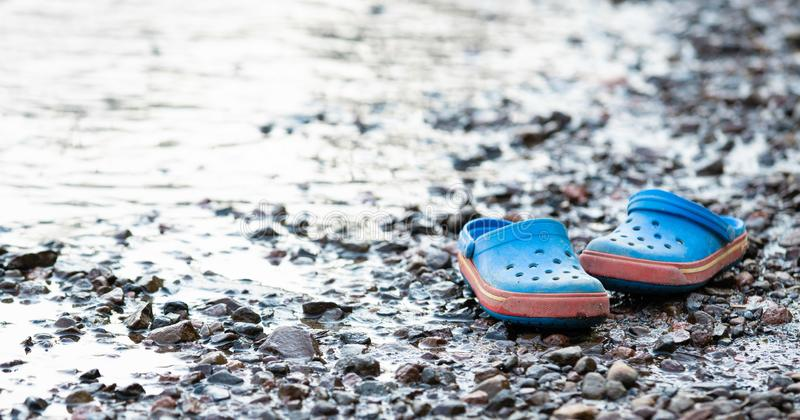 Pair of blue flip flops on the beach. Filled with tiny stones and pebbles royalty free stock images