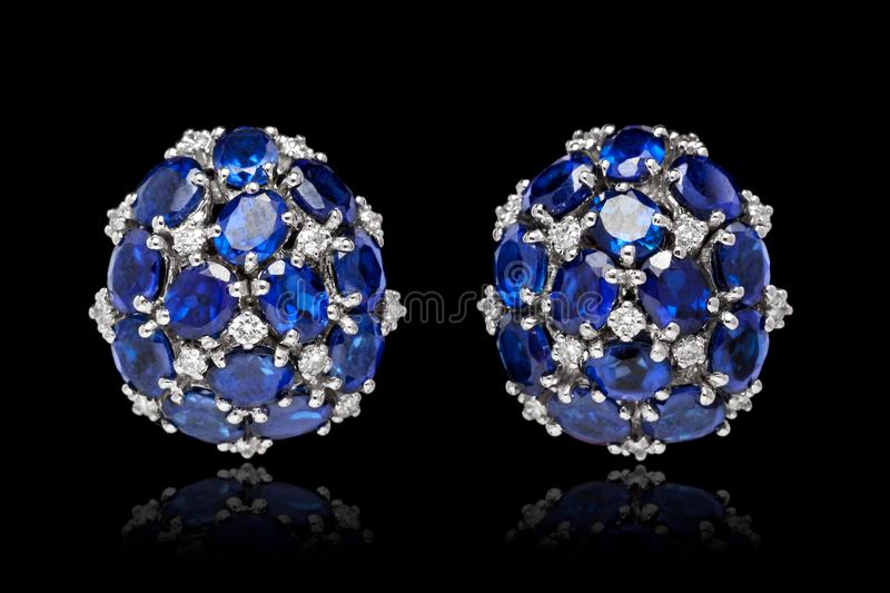 Pair of Blue gem stone Earrings with diamonds isolated over black stock photo