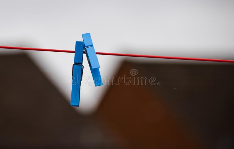 Plastic clothes pegs. A pair of blue plastic clothes pegs on a red clothes line stock photo