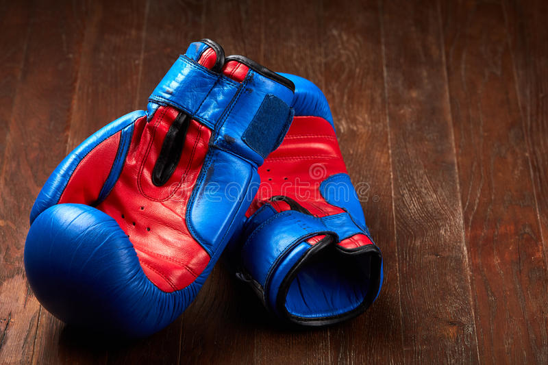 Pair of blue and red boxing gloves lying on the brown wooden table. stock photo
