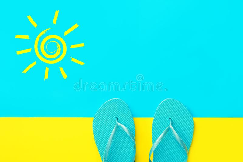 Pair of blue rubber beach slippers on duotone bright yellow cyan background. Imitation of sand and sea. Hand drawn doodle sun. Pair of blue rubber beach slippers stock images