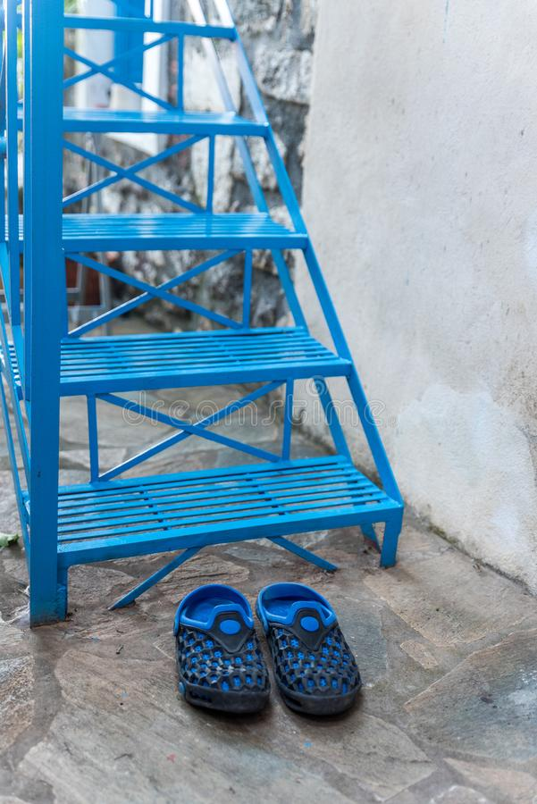 Pair of blue rubber shoes in front of blue stairs. Pair of blue rubber shoes in front of blue metal stairs in Greek Village royalty free stock photos