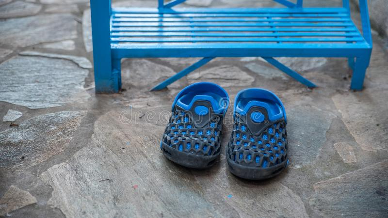 Pair of blue rubber shoes in front of blue stairs. Pair of blue rubber shoes in front of blue metal stairs in Greek Village stock photography