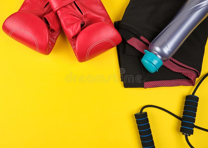 Pair of blue sneakers, red leather boxing gloves and a black jump rope. Yellow sports background, copy space royalty free stock image