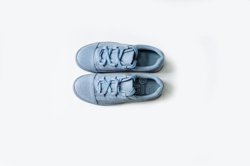 Pair of blue suede shoes with thick laces on a white background royalty free stock photo