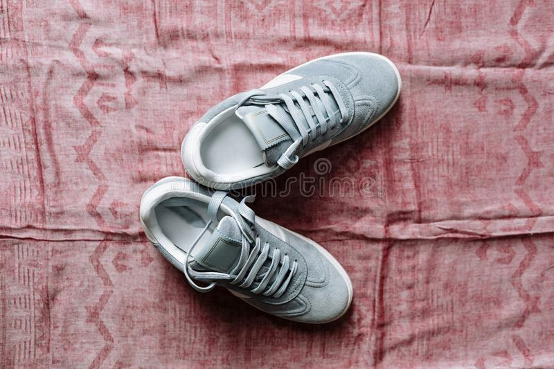 A pair of blue suede sneakers on a white sole with white accents on a pink background stock photo