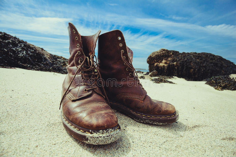Pair of boots on the beach. A pair of hiking boots on the beach in summer stock images