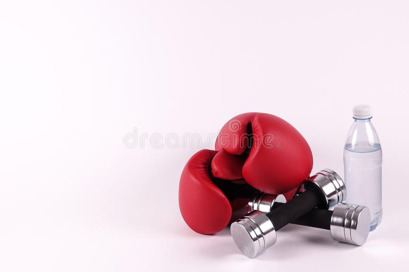 A pair of boxing gloves and dumbbells and a bottle of water stock image