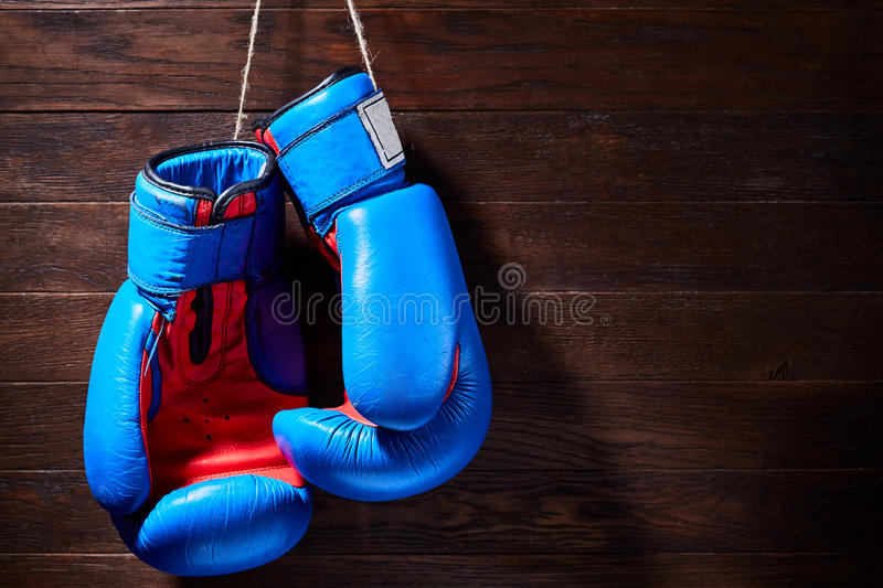 A pair of bright blue and red boxing gloves hangs against wooden background. Boxing backgrounds and still-life. Colorful accessories for sport. Horizontal royalty free stock photos