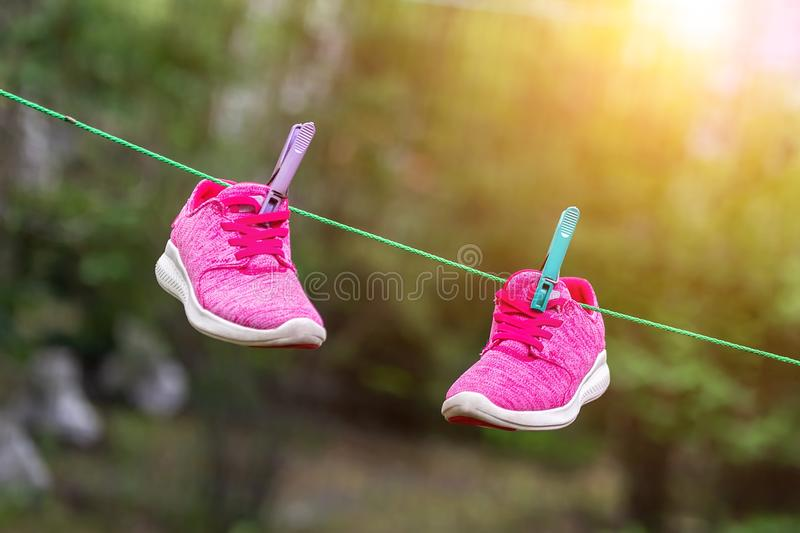 Pair of bright sport fitness sneakers hanged on clothespin at backyard after laundry outdoors. Preparartion for running stock photo