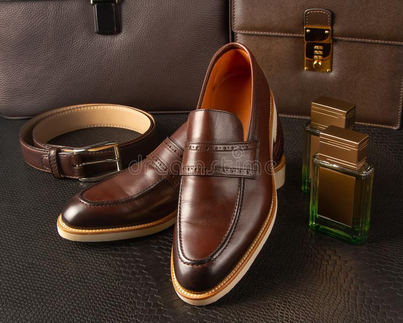 A pair of brown men`s shoes with a bright sole and accessories of a business man against the background of men`s briefcases stock photos