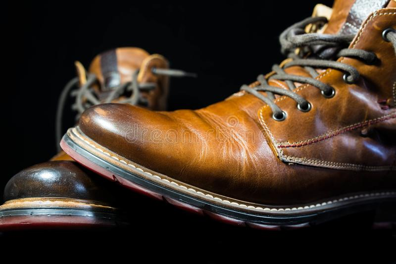 A pair of brown real leather boot isolated on black. Background stock images