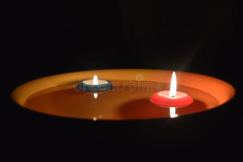 Floating burning candles in night. A pair of burning candles on black background with reflection on water surface. A suitable shot to express sadness. Romantic stock image