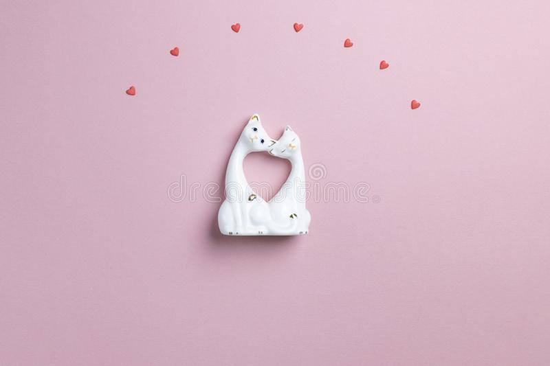 A pair of cats in love overhead small hearts made of sweet candies. Valentine and love concept, February 14, postcard. Pink royalty free stock image
