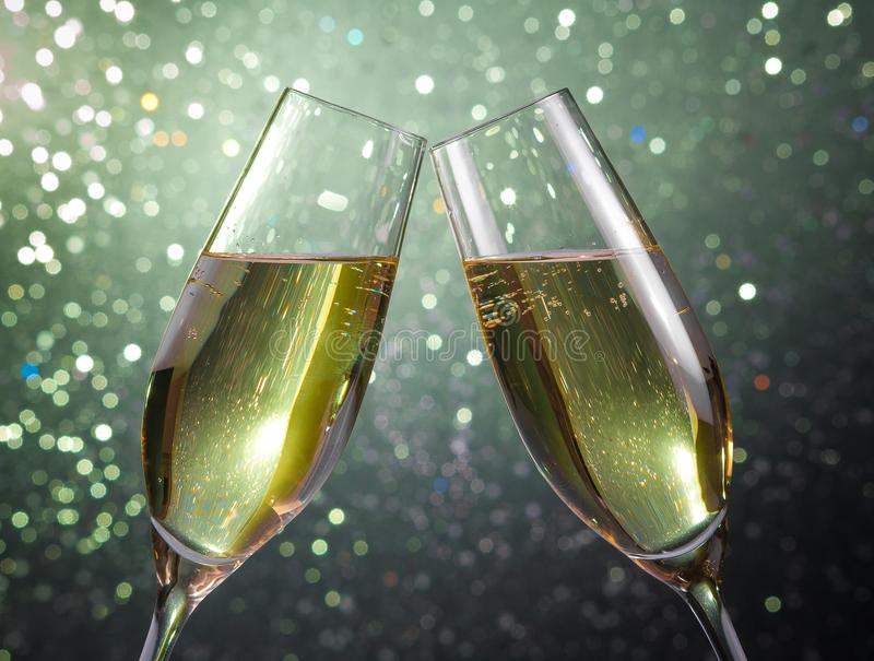 Pair of a champagne flutes with gold bubbles on green light bokeh background stock image
