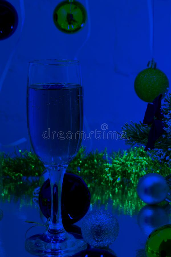 Pair of champagne flutes with gold bubbles make cheers on blue tint light bokeh background.  royalty free stock image