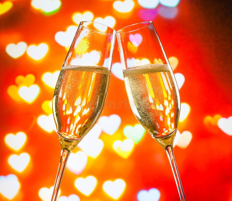 A pair of champagne flutes with golden bubbles on hearts bokeh background stock images