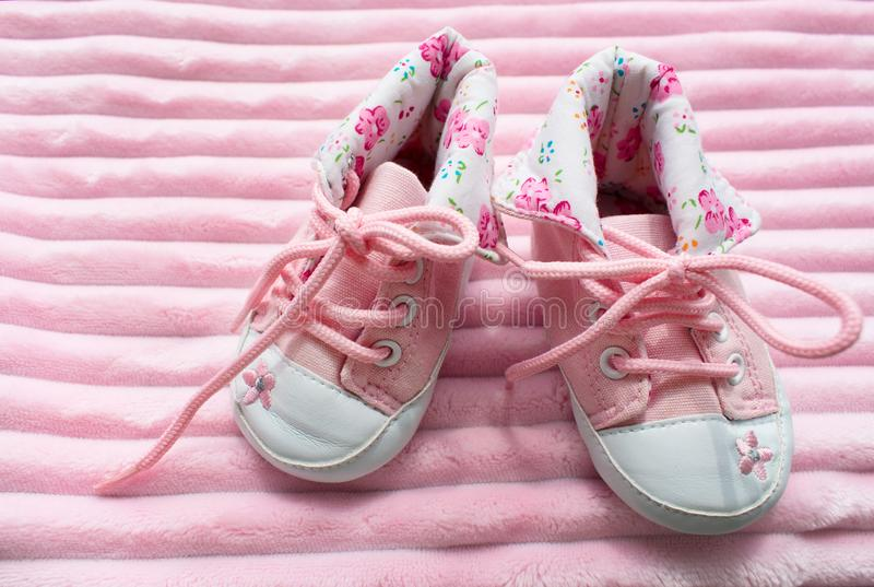 A pair of children`s sneakers for girls on a pink background royalty free stock image