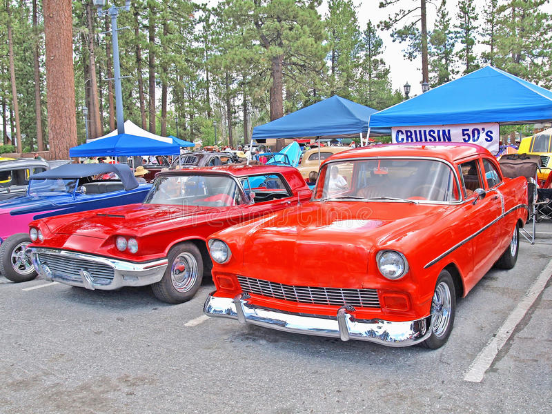 A Pair Of Classics. Pictured are a red colored 1959 Ford Thunderbird and an orange colored 1956 Chevrolet stock photo